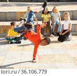 Mulatto b-boy performing stunts on city street. Стоковое фото, фотограф Яков Филимонов / Фотобанк Лори