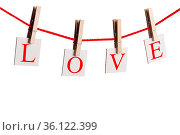 Clothes pegs and word LOVE on papers on rope isolated on white background... Стоковое фото, фотограф Zoonar.com/Ivan Mikhaylov / easy Fotostock / Фотобанк Лори