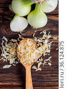 Onion bulb, shallot, dry onion flakes spilled over wooden spoon on... Стоковое фото, фотограф Zoonar.com/Oksana Shufrych / easy Fotostock / Фотобанк Лори