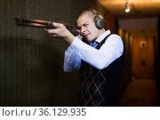 Concentrated man practicing shotgun shooting at firing range. Стоковое фото, фотограф Яков Филимонов / Фотобанк Лори