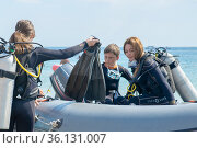 Anapa, Russia - June 20, 2019: A group of tourists divers in a rubber boat sail on the sea. copy space. Редакционное фото, фотограф Александр Сергеевич / Фотобанк Лори