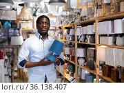 African american man choosing light fixture in furnishings store. Стоковое фото, фотограф Яков Филимонов / Фотобанк Лори