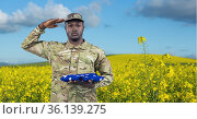 Composition of saluting male soldier with holding folded american flag, on rapeseed field. Стоковое фото, агентство Wavebreak Media / Фотобанк Лори