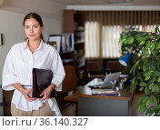 Portrait of a young girl standing with a folder of documents in a office. Стоковое фото, фотограф Яков Филимонов / Фотобанк Лори