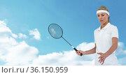 Caucasian female badminton player holding racket against clouds in blue sky. Стоковое фото, агентство Wavebreak Media / Фотобанк Лори