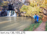 the famous waterfall atysh flowing from a karst funnel in the Ural mountains of Bashkortostan on an autumn sunny day. Стоковое фото, фотограф Акиньшин Владимир / Фотобанк Лори