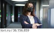 Portrait of caucasian businesswoman with brown hair wearing face mask in modern office. Стоковое видео, агентство Wavebreak Media / Фотобанк Лори