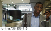 African american businessman talking on smartphone in corridor of modern office. Стоковое видео, агентство Wavebreak Media / Фотобанк Лори