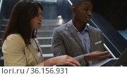 Diverse businessman and businesswoman talking and using laptop in corridor of modern office. Стоковое видео, агентство Wavebreak Media / Фотобанк Лори