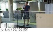 Caucasian businesswoman talking on smartphone in corridor in modern office. Стоковое видео, агентство Wavebreak Media / Фотобанк Лори