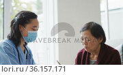 Asian female nurse wearing face mask bringing soup to senior female patient sitting in hospital bed. Стоковое видео, агентство Wavebreak Media / Фотобанк Лори