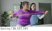 Asian female physiotherapist helping female patient exercise arms with exercise band at surgery. Стоковое видео, агентство Wavebreak Media / Фотобанк Лори