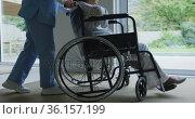 Asian female doctor pushing female patient in wheelchair at hospital. Стоковое видео, агентство Wavebreak Media / Фотобанк Лори