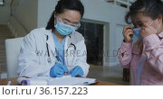 Asian female nurse wearing face mask and gloves writing during consultation with female patient. Стоковое видео, агентство Wavebreak Media / Фотобанк Лори