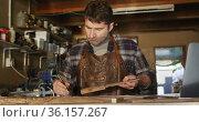 Focused caucasian male knife maker in workshop holding tool and making notes. Стоковое видео, агентство Wavebreak Media / Фотобанк Лори