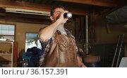 Caucasian male knife maker in workshop standing at desk and drinking coffee. Стоковое видео, агентство Wavebreak Media / Фотобанк Лори