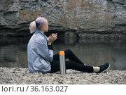Teenage girl hiker sits with a mug on the river bank looking at the coastal cliffs. Стоковое фото, фотограф Евгений Харитонов / Фотобанк Лори