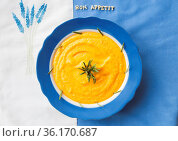 Pumpkin soup in a blue plate with rosemary on a napkin with flowers... Стоковое фото, фотограф Zoonar.com/Sergiy Artsaba / easy Fotostock / Фотобанк Лори