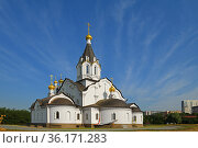 Stone white church of Holy Apostles Constantine and Elena against background of beautiful blue sky with clouds. Moscow, Russia. Редакционное фото, фотограф Валерия Попова / Фотобанк Лори
