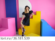 Young pleasing woman in a black hat and dress poses in the studio against a pink wall. Стоковое фото, фотограф Алексей Кузнецов / Фотобанк Лори