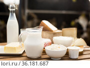 jug of milk, bottle of kefir, cottage cheese, cream and yogurt in bowl, cheese, butter on table in barn. Стоковое фото, фотограф Татьяна Яцевич / Фотобанк Лори