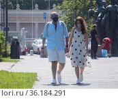 Пара в молодых людей в защитных масках гуляет в парке. Редакционное фото, фотограф Сайганов Александр / Фотобанк Лори