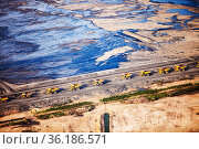 Massive dump trucks queuing to load with tar sand in front of a toxic wasteland. Syncrude mine, Athabasca, Alberta, Canada, 2012. Стоковое фото, фотограф Ashley Cooper / Nature Picture Library / Фотобанк Лори