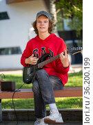 Guitarist playing guitar in summer park. Стоковое фото, фотограф Евгений Ткачёв / Фотобанк Лори