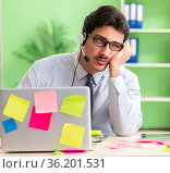 Young help desk operator working in office with many conflicting. Стоковое фото, фотограф Elnur / Фотобанк Лори