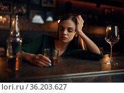 Stressed woman drinks alcohol beverage in bar. Стоковое фото, фотограф Tryapitsyn Sergiy / Фотобанк Лори