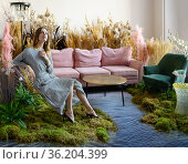 Young woman posing in a living room in the middle of tall grass. Стоковое фото, фотограф Алексей Кузнецов / Фотобанк Лори