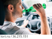 Drunk driver drinking behind the steering wheel of a car. Стоковое фото, фотограф Zoonar.com/Tomas Anderson / easy Fotostock / Фотобанк Лори