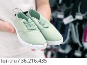 Green children's sneakers in the men's hands. Стоковое фото, фотограф Володина Ольга / Фотобанк Лори