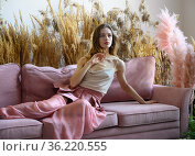 Pleasant woman sitting on a sofa in a room in tall grass. Стоковое фото, фотограф Алексей Кузнецов / Фотобанк Лори