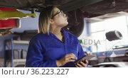Female mechanic using digital tablet standing under a car at a car service station. Стоковое видео, агентство Wavebreak Media / Фотобанк Лори