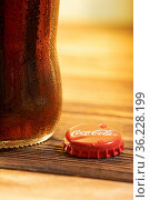 Close-up of cola in a glass bottle on wooden table. Стоковое фото, фотограф Александр Иванов / Фотобанк Лори
