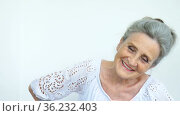 Beautiful old grandmother with grey hair and face with wrinkles is looking at the camera with smile on white background, mothers day, happy retirement. Стоковое видео, видеограф Ольга Балынская / Фотобанк Лори