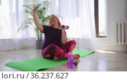 Fitness training - blonde overweight woman sits on yoga mat and taking a selfie with a dumbbell. Стоковое видео, видеограф Константин Шишкин / Фотобанк Лори