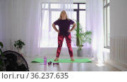 Fitness training - blonde overweight woman doing fitness exercises - warming up her body with circle movements. Стоковое видео, видеограф Константин Шишкин / Фотобанк Лори