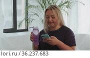 Blonde overweight woman using her phone and drinks water after fitness training. Стоковое видео, видеограф Константин Шишкин / Фотобанк Лори