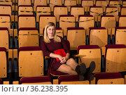 Reflective woman sitting alone in empty cinema. Стоковое фото, фотограф Яков Филимонов / Фотобанк Лори