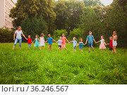 The cute little kids follow female caregiver holding hands. The children... Стоковое фото, фотограф Zoonar.com/Oksana Shufrych / easy Fotostock / Фотобанк Лори