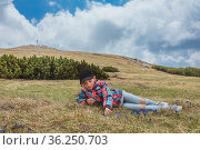 Young girl laying on meadow picking blue bladder gentian in alpine... Стоковое фото, фотограф Zoonar.com/Silvia Eder / easy Fotostock / Фотобанк Лори