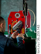 Electrician with stripper installing energy system on machinery industry... Стоковое фото, фотограф Zoonar.com/Jax_Sorax / easy Fotostock / Фотобанк Лори