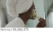 Portrait of african american attractive woman applying face mask in bathroom. Стоковое видео, агентство Wavebreak Media / Фотобанк Лори
