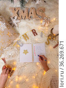 A woman writes out a Christmas shopping list. Стоковое фото, фотограф Zoonar.com/Leah-Anne Thompson / easy Fotostock / Фотобанк Лори