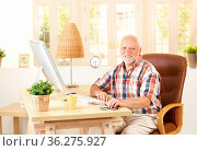 Senior man sitting at desk by computer at home, looking at camera... Стоковое фото, фотограф Zoonar.com/StockLite / easy Fotostock / Фотобанк Лори