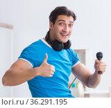 Young handsome man singing karaoke at home. Стоковое фото, фотограф Elnur / Фотобанк Лори
