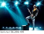 Young man rock musician in lights of stage. Стоковое фото, фотограф Zoonar.com/Aleksandr Khakimullin / easy Fotostock / Фотобанк Лори