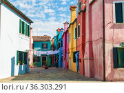 A courtyard on the island of Burano with bright colorful houses, the island quarter of Venice, on a sunny summer day. Venice, Italy (2017 год). Редакционное фото, фотограф Наталья Волкова / Фотобанк Лори